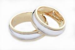 Due anelli dorati di nozze isolati su bianco Fotografia Stock