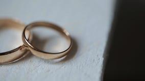 Due anelli dorati si trovano sulla tavola di legno dipinta nel colore bianco video d archivio