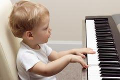 Due anni biondi svegli di bambino che gioca sul piano elettronico immagini stock libere da diritti