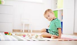 Due anni del bambino che si siede sul pavimento con i cubi di legno Immagini Stock