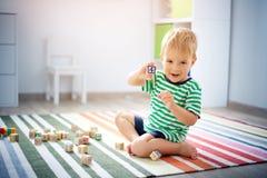 Due anni del bambino che si siede sul pavimento con i cubi di legno Fotografia Stock