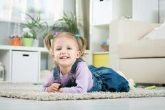 Due anni del bambino si trova sul pavimento Immagine Stock