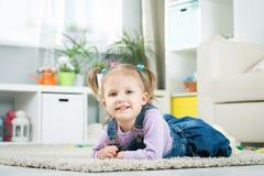 Due anni del bambino si trova sul pavimento Fotografia Stock