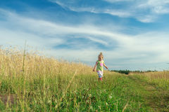 Due anni della ragazza bionda del bambino che cammina a piedi sulla strada non asfaltata fra il giacimento di cereale Immagini Stock