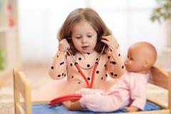 Due anni della ragazza che gioca al dottore con la bambola nella scuola materna Fotografia Stock
