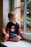 Due anni della ragazza del bambino dalla finestra Fotografie Stock