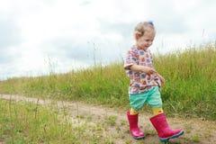 Due anni della ragazza del bambino in età prescolare che cammina a piedi sulla strada non asfaltata di estate del campo dell'azie Fotografia Stock