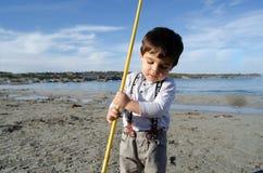 Due anni svegli del ragazzo che gioca con la rete da pesca il giorno soleggiato sulla spiaggia del mare immagine stock