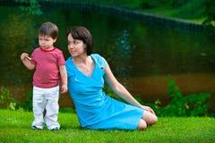 Due anni svegli del ragazzo con la sua giovane mamma in sosta Fotografia Stock