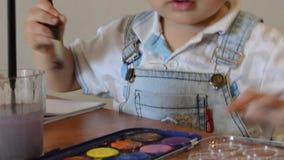 Due anni svegli della pittura del ragazzo con i colori di acqua stock footage