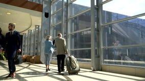Due anziani che camminano con la valigia archivi video