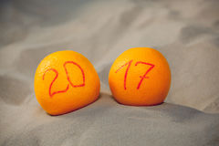 Due arance mature si trovano nella sabbia sulla spiaggia, essi stavano scrivendo il numero in onore di 2017 Fotografie Stock Libere da Diritti