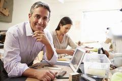 Due architetti che fanno i modelli in ufficio facendo uso della compressa di Digital Immagini Stock
