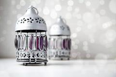 Due argento, misero, d'annata, supporti di candela di stile sul contesto brillante bianco del bokeh Immagine Stock