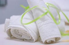 Due asciugamani bianchi rotolati e fissati con il legame verde sulla tavola di massaggio fotografia stock