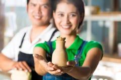 Asiatici con terraglie handmade nello studio dell'argilla Immagine Stock