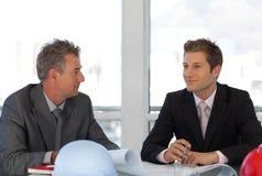 Due assistenti tecnici che esaminano le cianografie in ufficio Fotografia Stock Libera da Diritti
