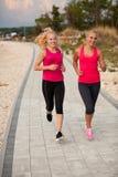 Due athlets che corrono sulla spiaggia - estate w delle donne di primo mattino Immagini Stock Libere da Diritti