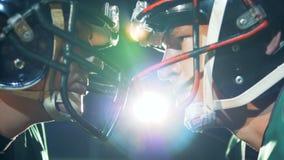 Due atleti di football americano stanno stando testa a testa su uno stadio video d archivio