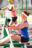 Due atleti femminili caucasici in attrezzatura professionale che ha esercizi fare un passo e di una rematura Immagine Stock Libera da Diritti