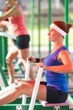 Due atleti femminili caucasici in attrezzatura professionale che ha esercizi fare un passo e di una rematura Fotografia Stock Libera da Diritti