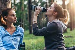 Due atleti femminili che parlano una rottura dopo la formazione dell'acqua potabile che si siede sulla terra nel parco Fotografie Stock