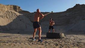 Due atleti maschii che si preparano insieme colpito la ruota con un tramonto di martellare nelle montagne sulla sabbia resistenza video d archivio