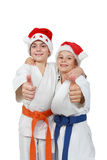 Due atleti nel cappuccio Santa Claus mostrano il dito eccellente Fotografia Stock