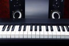 Due audio altoparlanti e primi piani stereo di chiavi del piano sul backgro scuro Immagine Stock