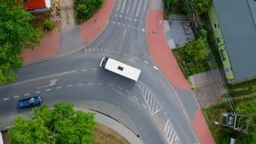 Due automobili che passano vicino attraverso l'intersezione curva in città, vista aerea video d archivio