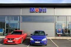 Due automobili davanti ad un negozio con il segno di Mobil fotografia stock