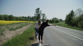 Due autostoppisti delle giovani donne stanno sulle attività collaterali e chiedono di fermare le automobili di passaggio archivi video