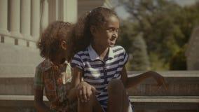 Due bambine adorabili che si rilassano sulle scale stock footage