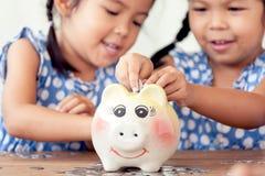 Due bambine asiatiche divertendosi per mettere moneta nel porcellino salvadanaio immagini stock