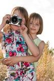 Due bambine che catturano maschera con la macchina fotografica di SLR Fotografie Stock Libere da Diritti