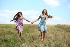 Due bambine che corrono nel campo di estate Fotografie Stock