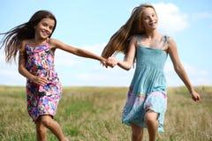 Due bambine che corrono nel campo di estate Fotografia Stock Libera da Diritti