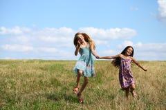 Due bambine che corrono nel campo di estate Immagini Stock Libere da Diritti