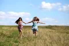 Due bambine che corrono nel campo di estate Immagini Stock
