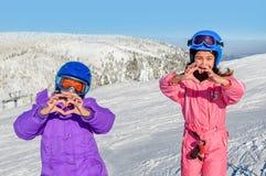 Due bambine che fanno cuore con le loro mani nella neve Immagine Stock Libera da Diritti