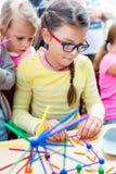 Due bambine che giocano con i lotti di plastica variopinta attacca il ki fotografia stock libera da diritti