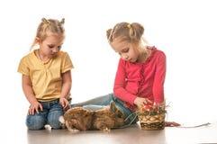 Due bambine che giocano con il coniglietto di pasqua su un fondo bianco Immagine Stock