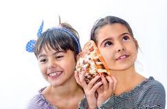 Due bambine che giudicano una conchiglia isolata su bianco Immagini Stock