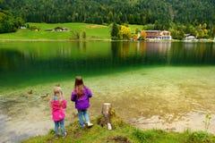 Due bambine che godono della vista delle acque verdi meravigliose del lago Hintersee Paesaggio stupefacente di autunno delle alpi Fotografia Stock Libera da Diritti