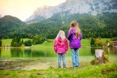 Due bambine che godono della vista delle acque verdi meravigliose del lago Hintersee Paesaggio stupefacente di autunno delle alpi Immagine Stock Libera da Diritti