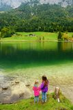 Due bambine che godono della vista delle acque verdi meravigliose del lago Hintersee Paesaggio stupefacente di autunno delle alpi Immagini Stock