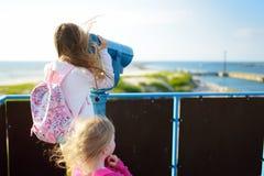 Due bambine che godono di una vista della riva del Mar Baltico all'estate Divertendosi nella stazione turistica di Ventspils Fotografie Stock Libere da Diritti