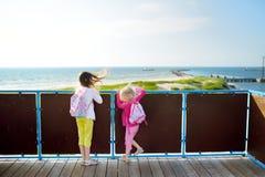 Due bambine che godono di una vista della riva del Mar Baltico all'estate Divertendosi nella stazione turistica di Ventspils Immagine Stock Libera da Diritti