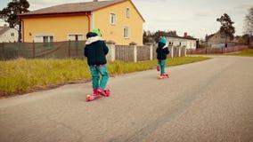 Due bambine che guidano i motorini su una strada campestre archivi video