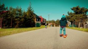 Due bambine che guidano i motorini su una strada campestre video d archivio